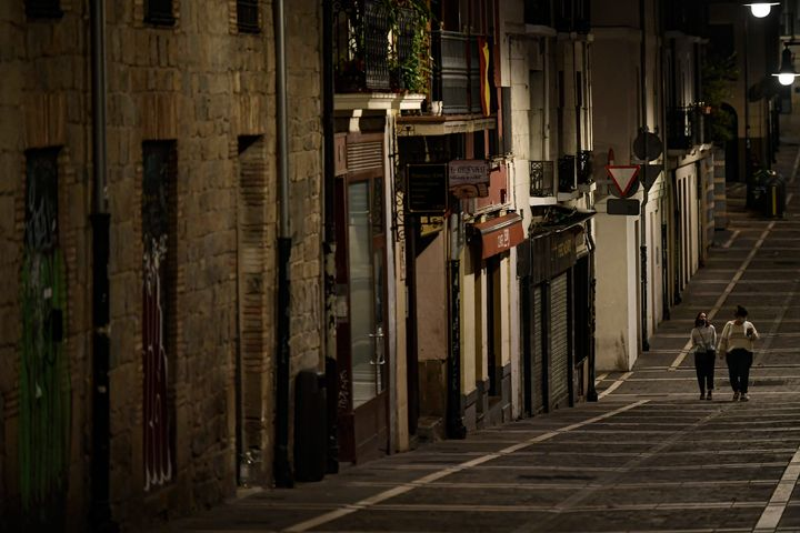 Residents wearing face mask protection are seen walking along an empty street in Pamplona, northern Spain, on Saturday.