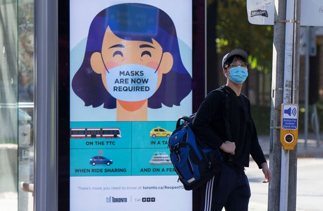 A man wearing a face mask waits to cross a street in Toronto on