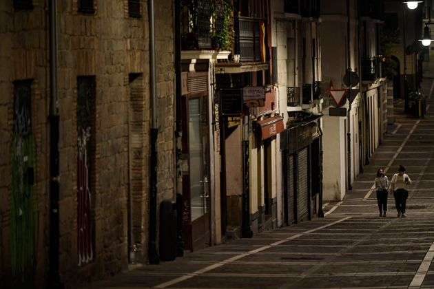 Residents wearing face masks as they walk along an empty Javier street, in Pamplona, northern Spain (AP...