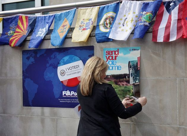 A consular staff member puts up voter-registration posters outside the U.S. consulate in Toronto on Sept....