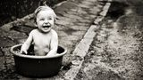 Happy baby boy  having bath in wash basin on a dirty and weathered sidewalk, in front of an old house.