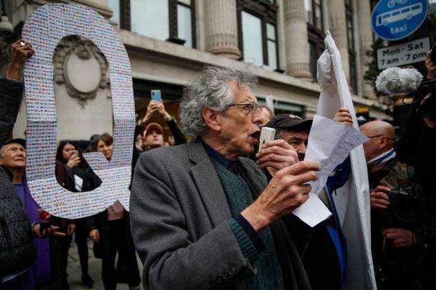 ロンドンで開かれた新型コロナウイルスの規制撤廃を求めるデモ。Qアノンのサインが掲げられている(2020年10月17日撮影)