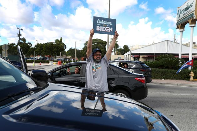 Un simpatizante del partido demócrata muestra una pancarta con el lema 'Cubanos con Biden' en...