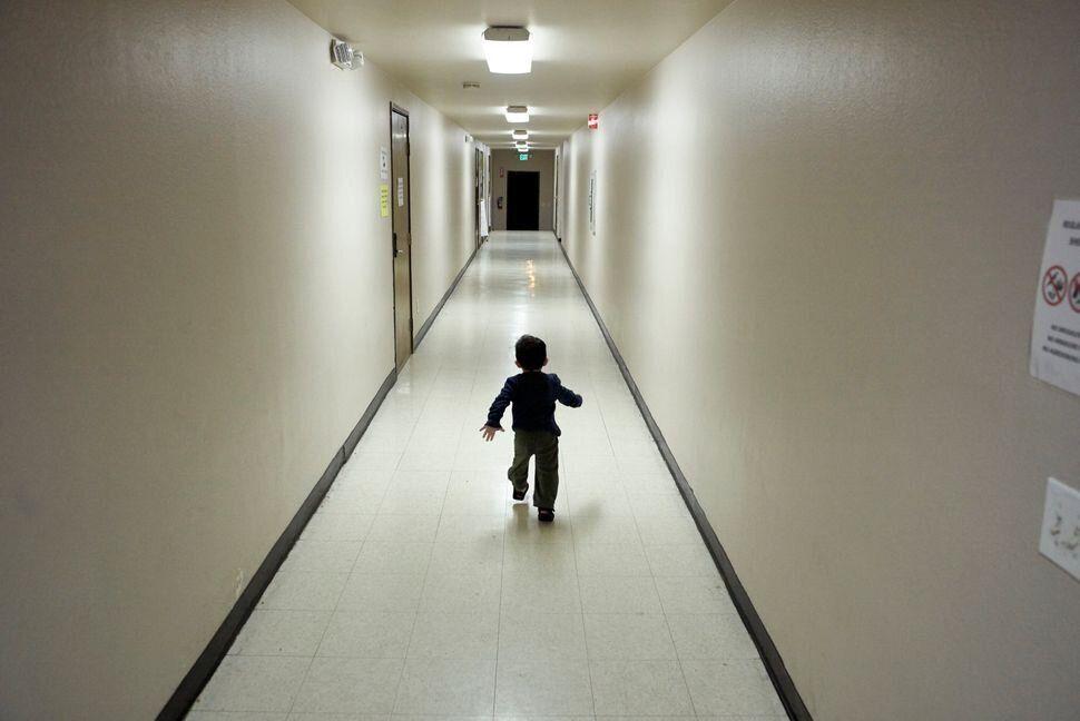 En esta foto de 2018, un niño refugiado de Centroamérica corre por el pasillo de un refugio...
