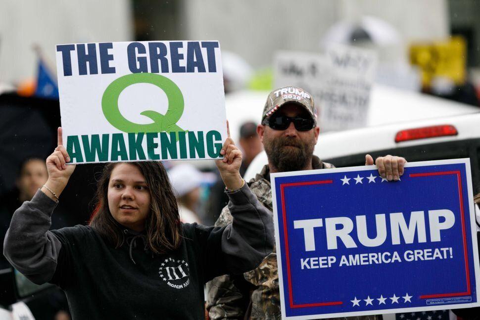 Teóricos de la conspiración de QAnon sostienen unas pancartas en apoyo a Trump en Oregón...