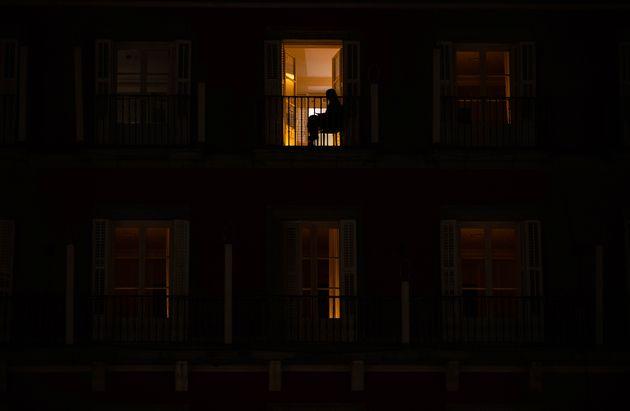 Una mujer se sienta en su balcón durante el horario de toque de queda en