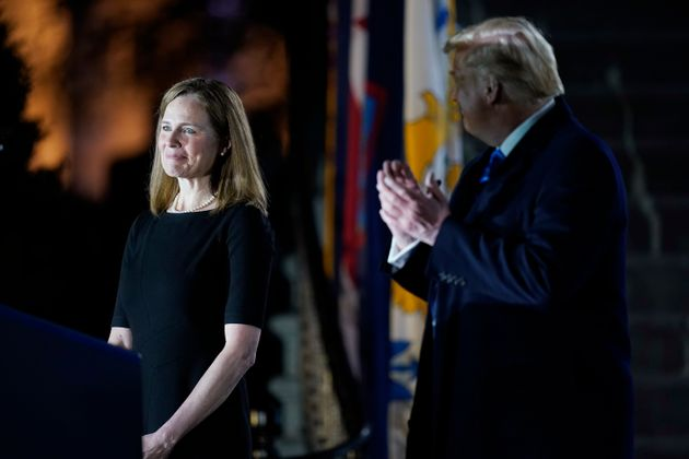 President Donald Trump looks toward Amy Coney Barrett, before Supreme Court Justice Clarence Thomas administers...