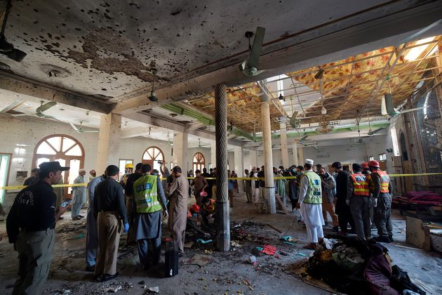 Security officials examine the site of a blast at a religious school in Peshawar on October 27, 2020....