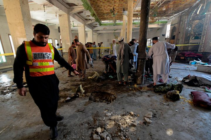 Rescue workers collect remains at the site of a blast in a religious school in Peshawar on Tuesday.