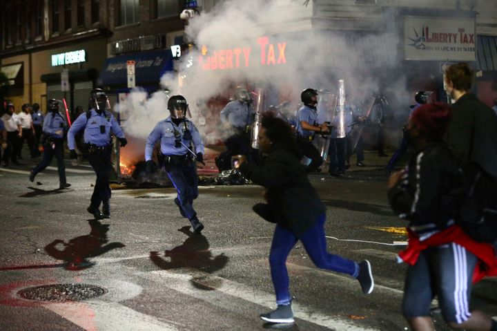 Police charge at a crowd along 52nd Street in West Philadelphia in the early hours of Tuesday, Oct. 27, 2020. Protesters gath