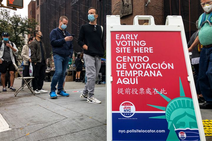Voters wait in line for a Houston Street polling site on the first day of early voting, Saturday, Oct. 24, 2020, in New York.