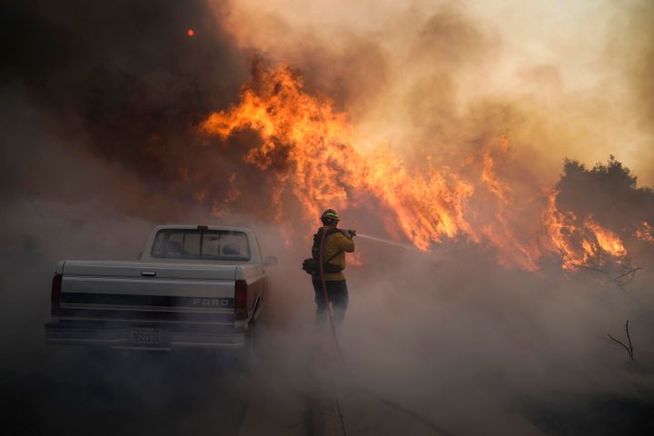 Firefighter Raymond Vasquez battles the Silverado Fire Monday, Oct. 26, 2020, in Irvine, Calif. A fast-moving wildfire forced