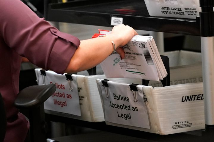 An election worker sorts vote-by-mail ballots at the Miami-Dade County Board of Elections, Monday, Oct. 26, 2020, in Doral, F