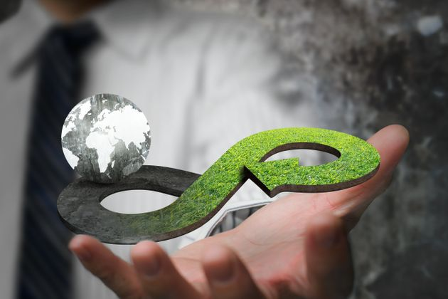 Green circular economy concept. Hand showing arrow infinity symbol with grass texture and