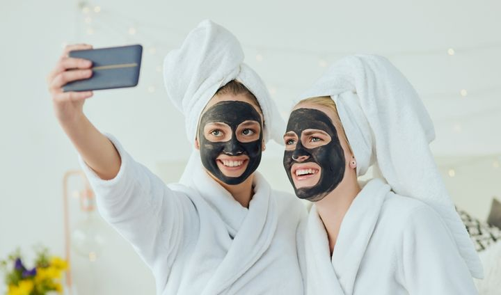 Cropped shot of two attractive young girl friends taking selfies while pampering themselves at home