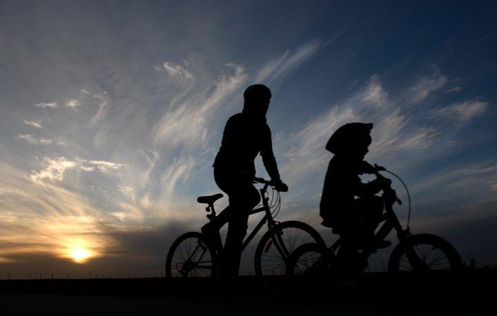 Ενας άνδρας κι ένα παιδί κάνουν ποδήλατο κατά μήκος της παραλίας Σεν Κίλντα στην Μελβούρνη.