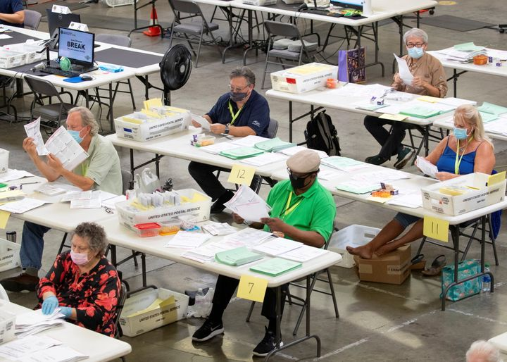 Election workers look over some of the hundreds of thousands of mail-in ballots as they are processed Oct. 16 at the Orange C
