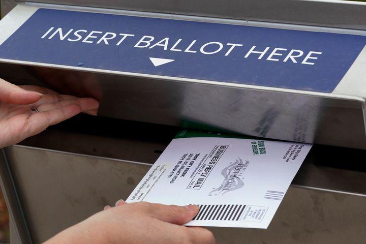 Nikki Schueller inserts her absentee voter ballot into a dropbox in Troy, Michigan, on Oct. 15.