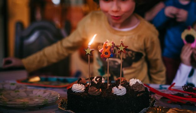 a boy blowing out candles in his birthday
