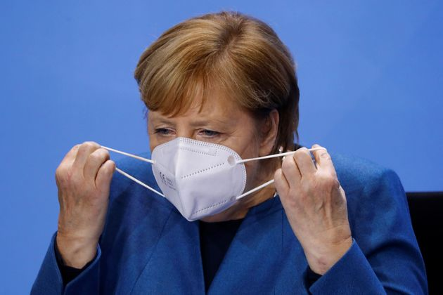 German Chancellor Angela Merkel putting on a mask.  (Photo by FABRIZIO BENSCH / POOL ...