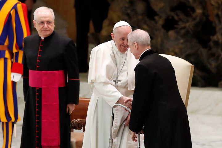 Pope Francis shakes hands with Monsignor Luis Maria Rodrigo Ewart as he arrives in the Paul VI Hall at the Vatican for his we