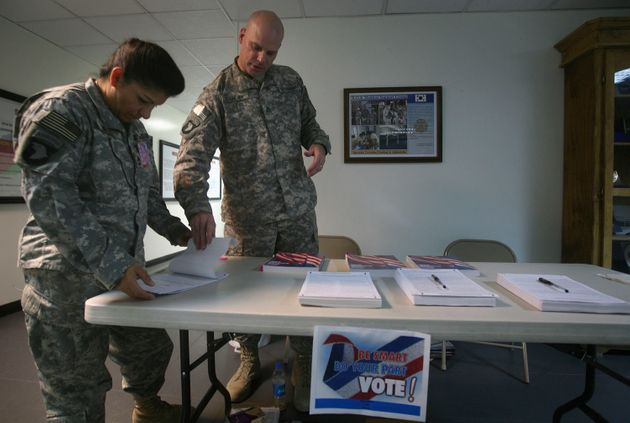 A U.S. service member (left) checks a ballot before filling it out at a U.S. military base in Afghanistan...