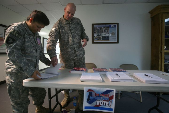 A U.S. service member (left) checks a ballot before filling it out at a U.S. military base in Afghanistan on Oct. 15, 2008. U