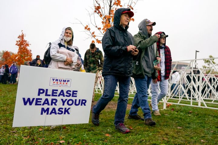 Supporters walk by a sign reminding them to wear a face mask as they arrive to hear President Donald Trump speak Monday at a