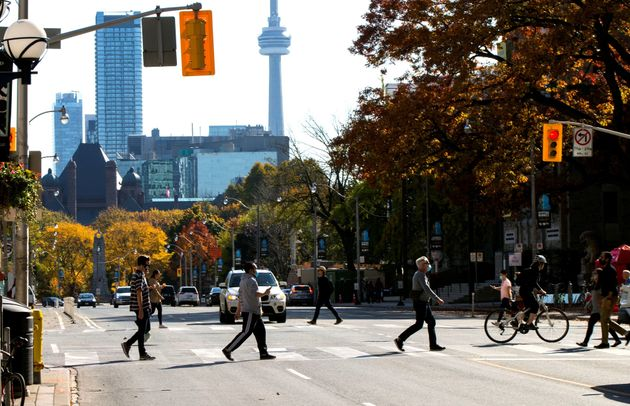 People wearing face masks cross a street in Toronto on Oct. 23,