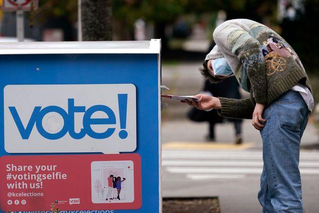ワシントン州シアトルで投票ボックスに票を入れる有権者(2020年10月28日)