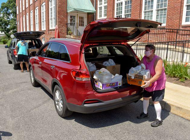 Unos voluntarios recogen cajas con comida de donaciones para el reparto de comida de la iglesia Salem...
