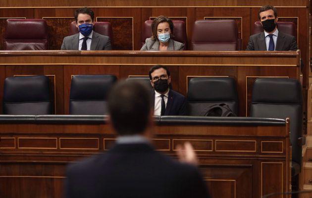 El líder del PP, Pablo Casado, de espaldas, se dirige al ministro de Sanidad, Salvador Illa, en...