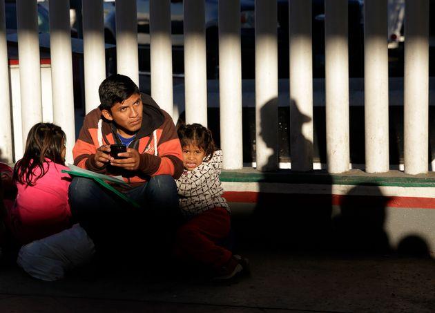 Un migrante sin identificar aguarda con sus hijos para ver si anuncian el número que le corresponde...