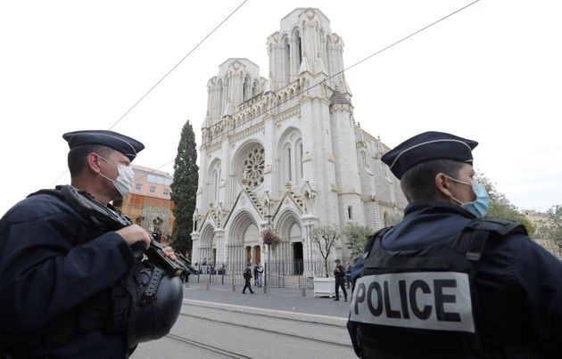 TOPSHOT - French policemen stand guard the site of a knife attack at the Basilica of Notre-Dame de Nice...