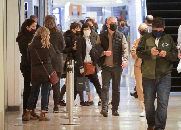 People wearing face masks walk inside a shopping mall in Vancouver on Oct. 22,