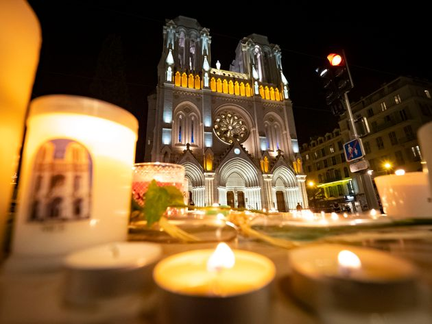 NICE, FRANCE - OCTOBER 29: People pay tribute at night in front of Notre Dame Basilica on October 29,...
