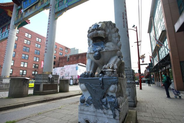 A statue is seen at the gates of Vancouver's Chinatown with racist graffiti covered, on May 21,