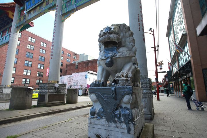 A statue is seen at the gates of Vancouver's Chinatown with racist graffiti covered, on May 21, 2020.<br />