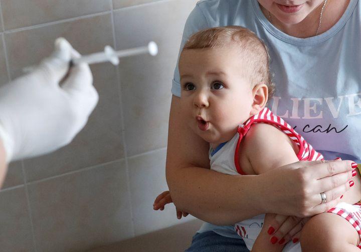 Un bebe, asustado ante una aguja con la que le van a vacunar