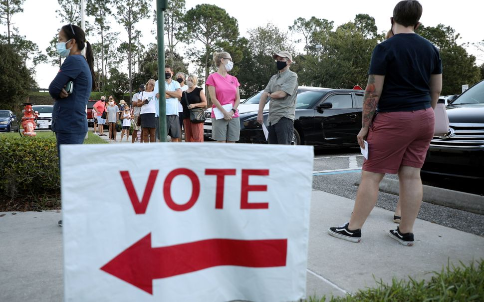 Voters line up to cast their ballots during early voting in Celebration, Florida, Oct. 25.