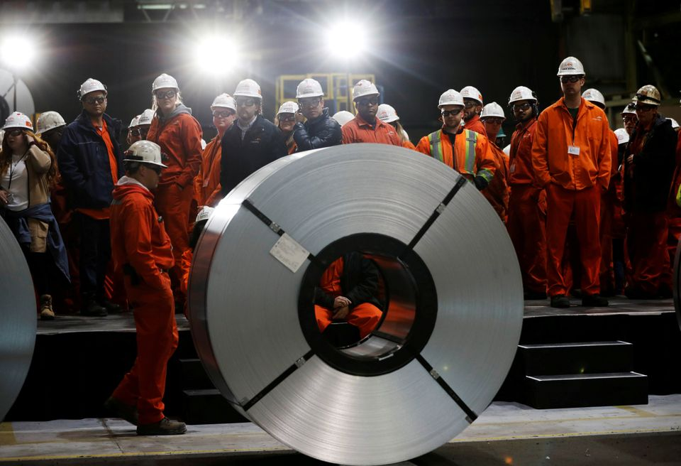 Workers stand behind rolls of steel at the ArcelorMittal Dofasco steel plant in Hamilton, Ontario, Canada,...