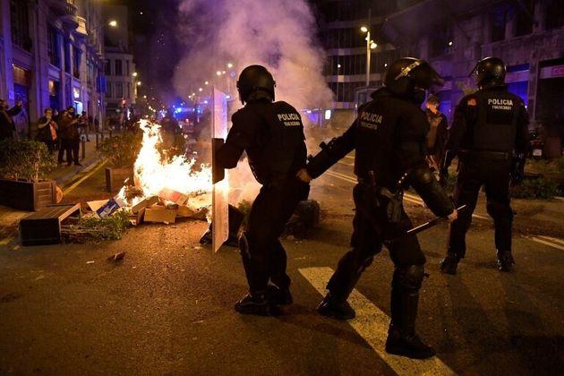 Varios Mossos avanzan ante un fuego provocado por
