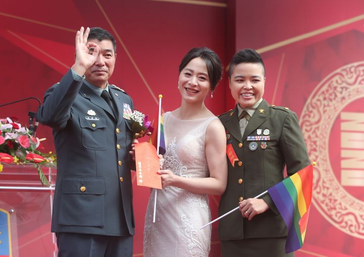 Yi Wang, right, Yumi Meng and General Chen Pao-Yu pose for a photo during a military mass wedding ceremony in Taoyuan city, n