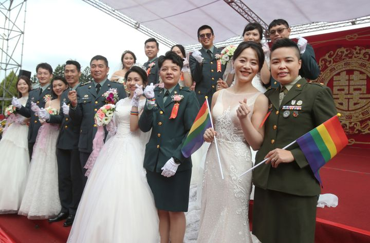 The two lesbian couples tied the knot in a mass ceremony held by Taiwan's military on Friday in a historic step for the islan