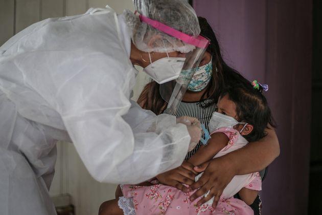 Enfermeira do SUS aplica vacina contra gripe em criança de comunidade ribeirinha a uma hora de...