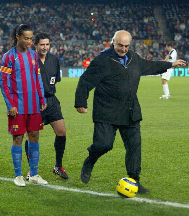 Barcelona, SPAIN: British actor Sean Connery (R) makes a ceremonial kick off with Brazilian player Ronaldinho...