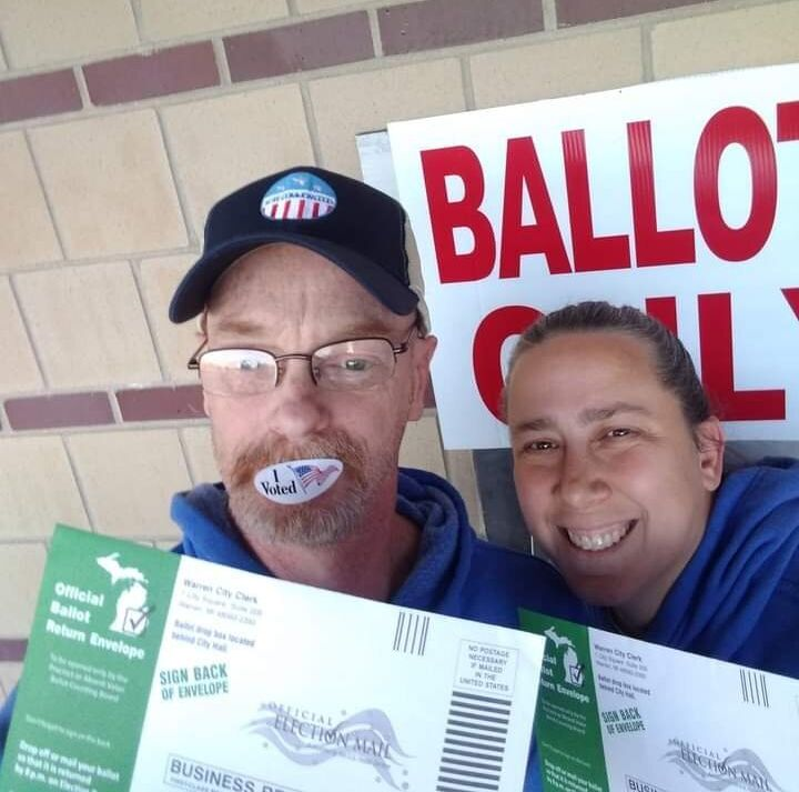 Ronald Hawthorne and his wife are pictured here voting early at a drop-off ballot box in Warren, Michigan.