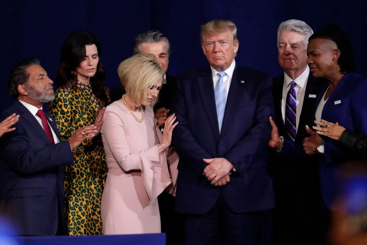 Faith leaders pray with President Donald Trump during a rally for evangelical supporters at the King Jesus International Mini