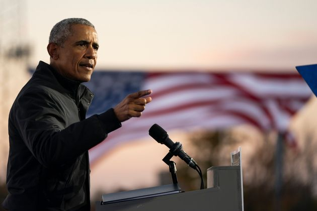 Former president Barack Obama speaks during a drive-in campaign rally with Democratic presidential nominee...