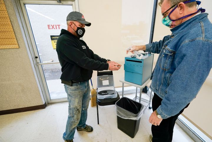 Chris Helps, of Earlham, Iowa, gets his hands sanitized by polling place volunteer Frank Hayer, right, during early voting, T